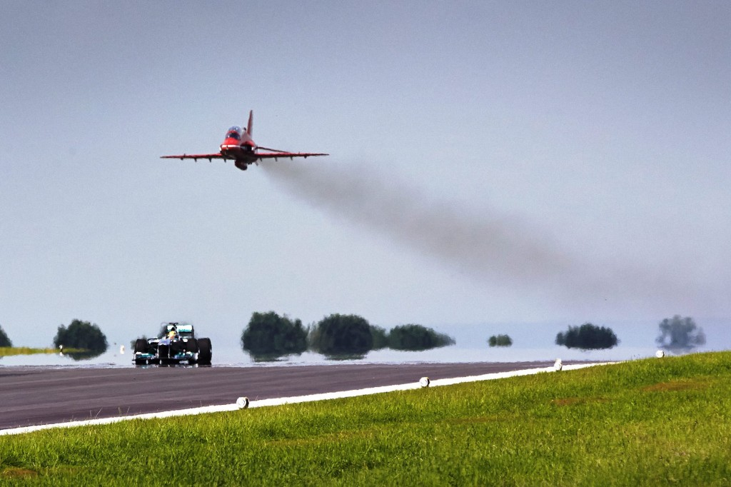 Red Arrow and Silver Arrow meet as Lewis Hamilton drives his Merceds AMG f1 car with an RAF Red Arrow Hawk jet above