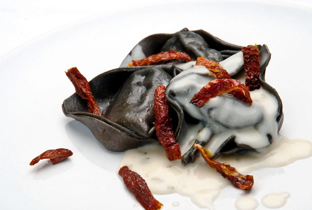 Black pasta filled with salmon in cava sauce with dried tomatoes for Iberia Business Class passengers