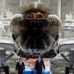 All Blacks rugby players Kieran Read and Andy Ellis walk the Black Air New Zealand Boeing 777 out of the paint hangar